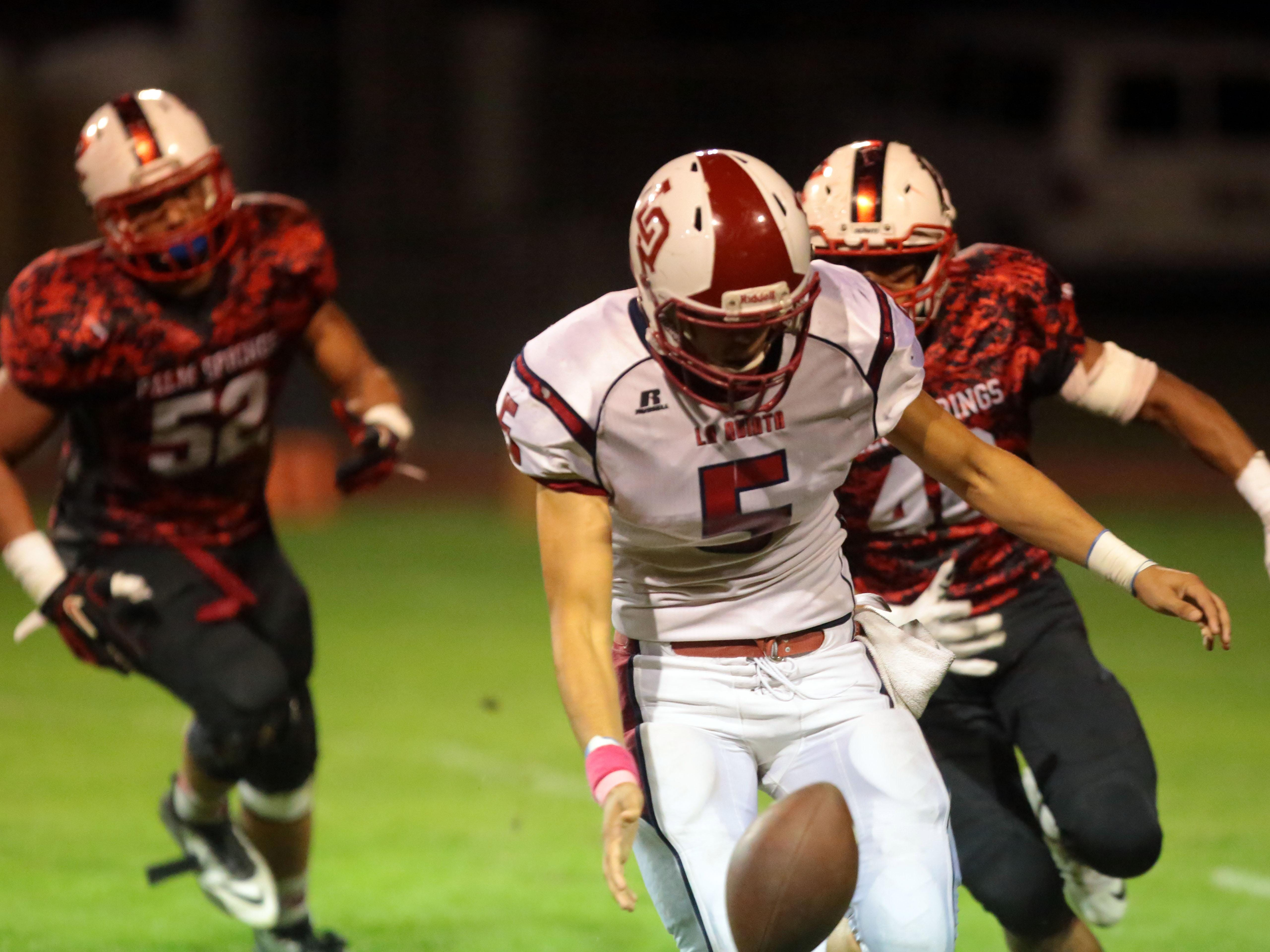 La Quinta quarterback Andrew Garcia drops and recovers the ball while being chased by Palm Springs' Brain Morales and Tyler Hawkins, left, on Friday in Palm Springs.