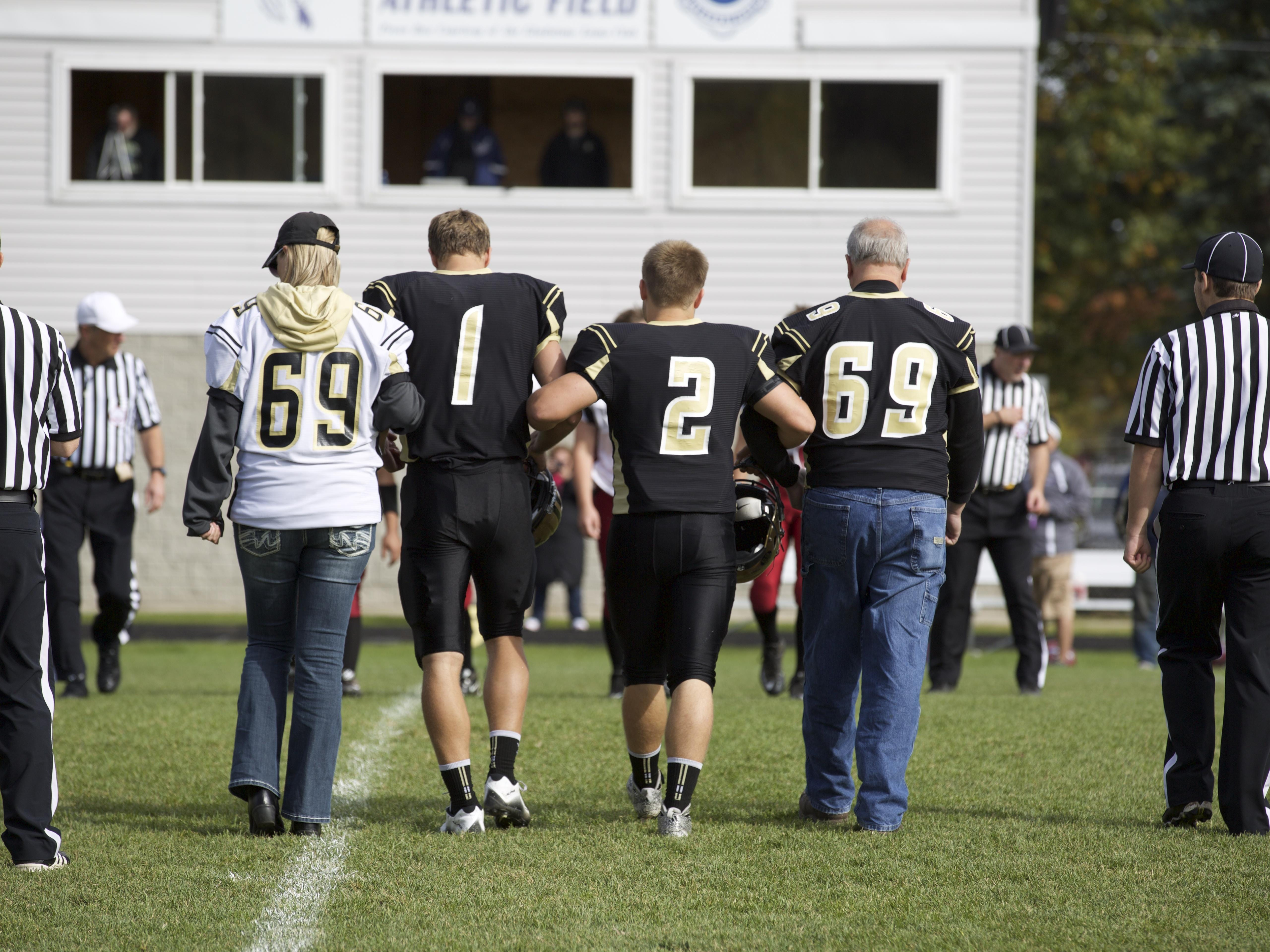 Mitchell Snyder's parents, wearing his No. 69, walk out with the St. Ignace captains before the game against Ironwood on Oct. 10. St. Ignace won, 69-12.