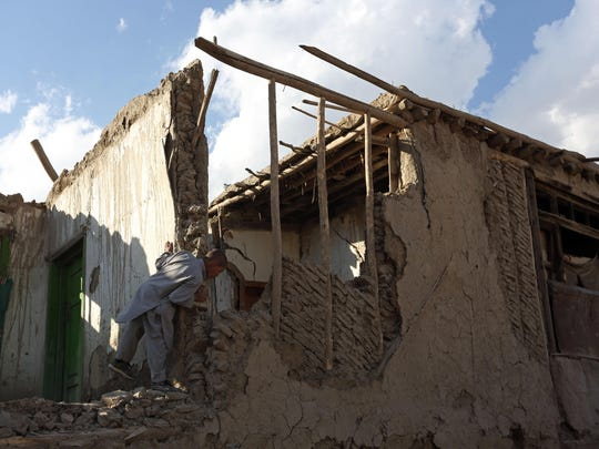 An Afghan boy looks at a damaged house following an earthquake, in Kabul, Afghanistan, Monday, Oct. 26, 2015. In Afghanistan's Takhar province, west of Badakhshan, at least 12 students at a girls' school were killed in a stampede as they tried to get out of the shaking buildings, a local official says. Sonatullah Taimor, the spokesman for the Takhar provincial governor, says another 30 girls have been taken to the hospital in the provincial capital of Taluqan. (AP Photo/Rahmat Gul)