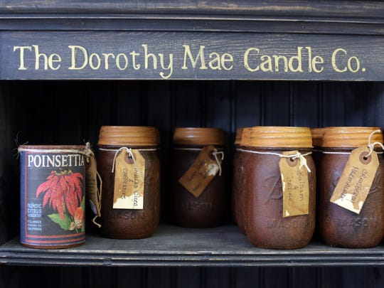 Candles are on display in New London. Chuck McClenning sells his primitive, country and folk art pieces at his Chasmacian Crafter store.