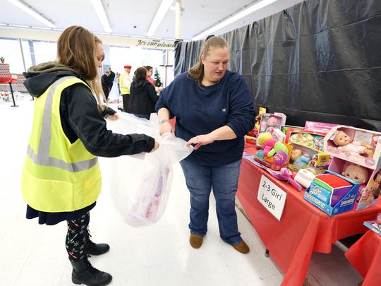 Volunteer Mandy Clapper, left, helps Elizabeth Fisher of Salem pick out gifts for her four children on Wednesday, in South Salem. The gifts were provided by the combined Salvation Army's Christmas Project Toy & Joy and Toys for Tots drives.
