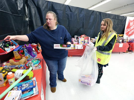 Volunteer Mandy Clapper, right, helps Elizabeth Fisher of Salem pick out gifts for her four children on Wednesday, Dec. 23, 2015, in South Salem. The gifts were provided by the combined Salvation Army's Christmas Project Toy & Joy and Toys for Tots drives.