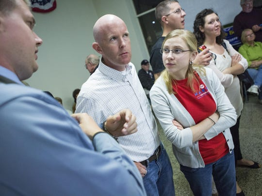 Tim Martin, center, stands beside his wife Melina Martin as they wait for election night results inside the Augusta County republican headquarters in Staunton on November 2, 2015.