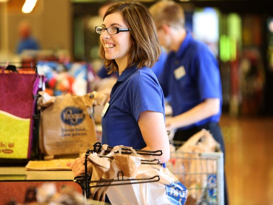 Tia Wicklund, smiles as she bags groceries while working at Kroger.