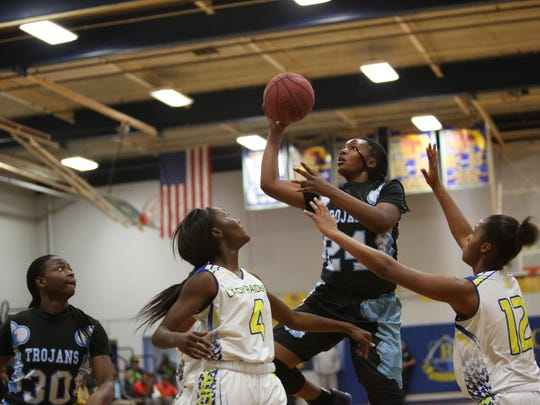 Jacksonville Ribault's Day'Neshia Banks soars for a runner over Rickards' Katelyn Marshall (4) and Tamia Riles (12) in a 68-32 win over Rickards on Friday night in a Region 1-5A final. Banks scored 30 points for the state's No. 1 team.