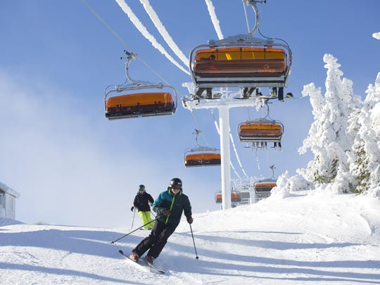 Skiers head up the and down the slopes at Okemo Mountain Resort. Riders heading up are on Sunburst Six, the first six-passenger bubble chairlift with heated seats in North America. It was built in 2014.