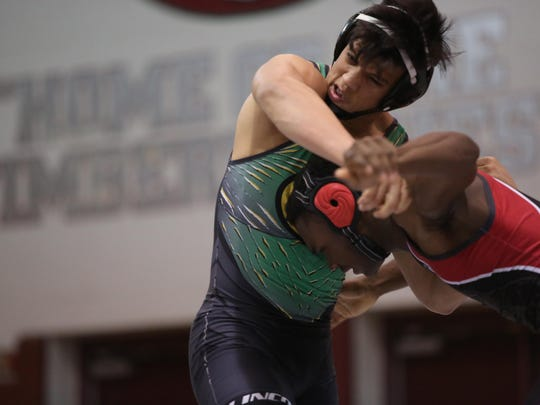 Leon's Thirkeal Lightsey, right, goes for the body of Lincoln's Isaac Gutierrez during Friday's District 1-2A tournament at Chiles. Lightsey won a district title with a pin of Gutierrez.