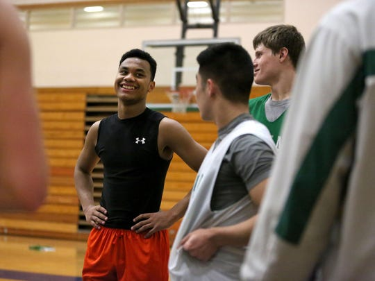 McKay High School junior Darrell Woods, left, jokes with teammates during practice on Monday, Jan. 5, 2015, in Salem, Ore. Woods has emerged as one of his team's best players. He was cut from the team as a freshman after on and off court issues, but has worked hard to make an impact.