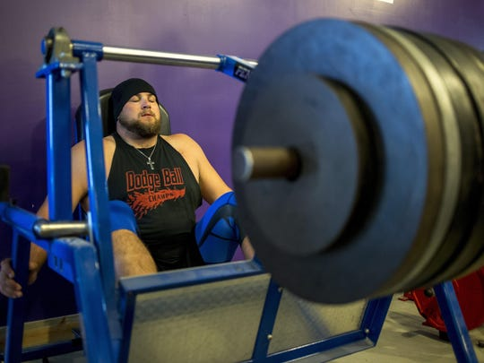 New Orleans Saints offensive lineman Tim Lelito concentrates as he prepares to lift 805 pounds on a pendulum hip press Wednesday at No Bull Strength and Performance in Fowlerville.