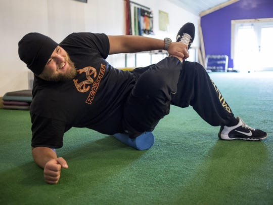 New Orleans Saints offensive lineman Tim Lelito stretches before working out Wednesday, April 13, 2016 at No Bull Strength and Performance in Fowlerville.