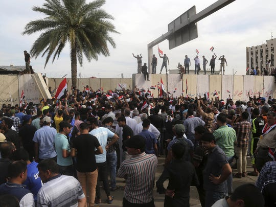Supporters of Shiite cleric Muqtada al-Sadr walk over the blast walls surrounding Baghdad's highly fortified Green Zone Saturday, April 30, 2016. Dozens of protesters climbed over the blast walls and could be seen storming the Parliament building, carrying Iraqi flags and chanting against the government.