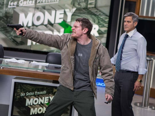 "Jack O'Connell, left, and George Clooney appear in a scene from ""Money Monster."""