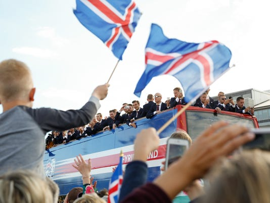 Icelandic soccer fans celebrate as their national team comes home to a hero's welcome from the Euro 2016 soccer championships in Reykjavik, Iceland, Monday July 4, 2016. (AP Photo/Brynjar Gunnarsson)