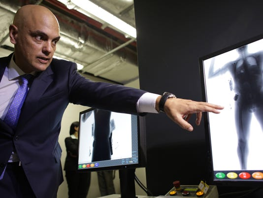"""In this Monday, July 25, 2016 photo, Brazil's Justice Minister Alexandre de Moraes points to the screen of a body scanner, during an inspection of safety procedures for the Rio 2016 Olympic Games, at the International Airport in Brasilia, Brazil. Moraes surprised many last week by saying the chances of a terror attack at the games were """"next to zero"""" and that the bigger concern is street crime. Just a day later, the federal police overseen by Moraes arrested 10 Brazilians allegedly belonging to an amateur cell that had professed allegiance to ISIS over the internet.  (AP Photo/Eraldo Peres)"""