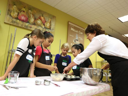 Isabella Mary, left, 10; Victoria Villegas, 10; Nora Terjeson, 8; and Luna Villegas, 8; learn how to make Creme Brulee muffins during a cooking class taught by Tori DeWolfe at Kelly's Home Center in Salem.
