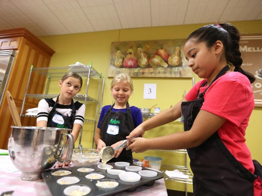 Isabella Mary, left, 10; Nora Terjeson, 8; and Victoria Villegas, 10, learn how to make Creme Brulee muffins during a cooking class taught by Tori DeWolfe at Kelly's Home Center in Salem.