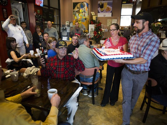 Eric Becker carries a cake out to Robert Reed, a World War II U.S. Navy veteran, for his 98th birthday surprise at EJ's Bayfront Cafe on Saturday in East Naples. Reed celebrated his birthday with his two friends, Ronn Ginn and Dave Marger, by flying to Naples from St. Petersburg for breakfast. Ginn orchestrated the surprise at the restaurant.