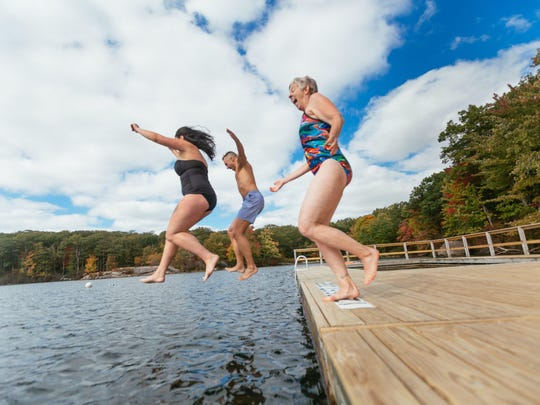 Harriman Outdoor Center guests jump into a swimming area in 64-acre Breakneck Pond last summer.