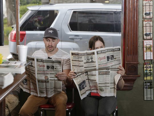 Melanie Carrier and Denis Mimeault, vacationing from Canada, check out the menu at the Ozark Café.