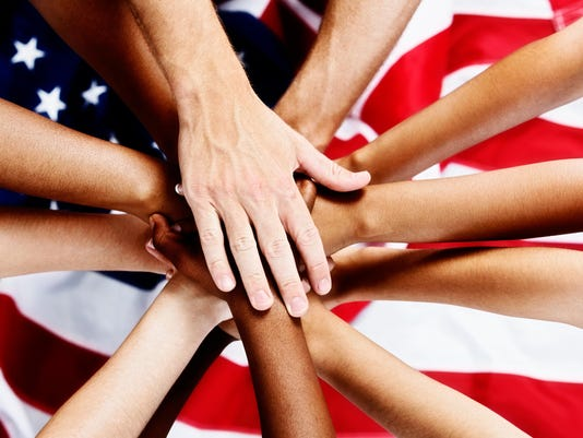 Many hands stacked patriotically on American flag