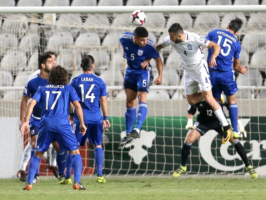 Cyprus' Fanos Katelaris, left, jumps for the ball with Greece' s Kostas Manolas during their World Cup Group H qualifying soccer match between Cyprus and Greece at GSP stadium in Nicosia, Cyprus, Saturday, Oct. 7, 2017. (AP Photo/Petros Karadjias)