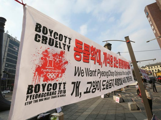 """In this Jan. 14, 2018, photo, a South Korean animal right activist attends a campaign opposing South Korea's culture of eating dog meat in Seoul, South Korea. Just weeks before the Olympics, a culture clash is taking place in Pyeongchang, and it's only partly about the anticipatory jitters before a swarm of foreigners arrives. There's a strain of unease as the government, desperate to measure up to an Olympic host city image, pushes for change in an indebted, aging backwater that relies on tourism and fisheries with no real industrial base. The Korean read """"We want Pyeongchang Olympic without dog meat."""" (AP Photo/Ahn Young-joon)"""