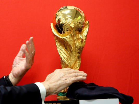 Cyprus' President Nicos Anastasiades unveils the FIFA World Cup trophy during its world tour at a stop at the international airport in the southern city of Larnaca, Cyprus, on Friday, Feb. 16, 2018. The trophy will visit some 50 countries as it make its journey round the world to Moscow for the start of the World Cup 2018 in Russia. (AP Photo/Petros Karadjias)