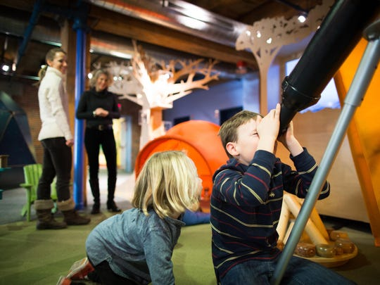 Kids can look into a telescope at the ECHO astronomy exhibit.