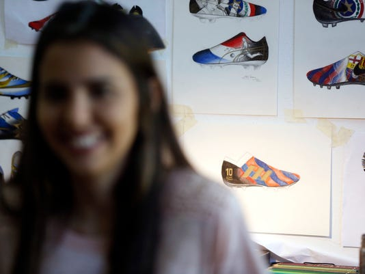 "In this Feb. 20, 2018 photo, Paraguayan artist Lilian Cantero smiles in her studio backdropped by her painting designs which she adds to soccer cleats to honor Argentine soccer player Lionel Messi, in San Lorenzo, Paraguay. ""I chose Messi because he's one of the greatest players in history, but also because of his own history - his childhood, which demanded so many sacrifices,"" Cantero said. (AP Photo/Jorge Saenz)"