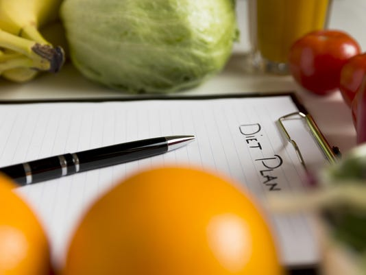 Sheet of Diet Plan and fresh products on wooden table
