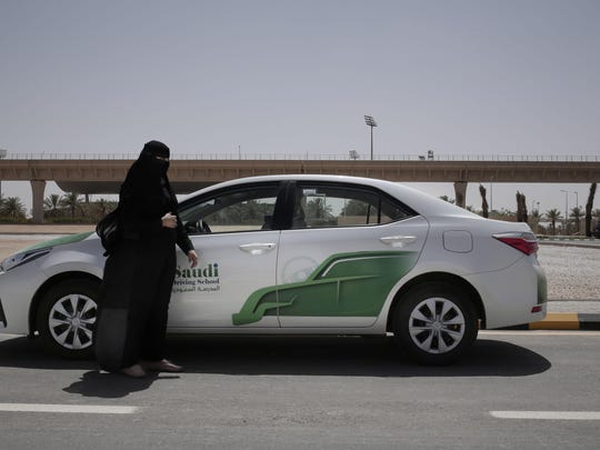 In this June 23, 2018 photo, 27-year old driving instructor Mabkhoutah al-Mari stands next to a test drivers car at the Saudi Driving School inside Princess Nora University in Saudi Arabia.