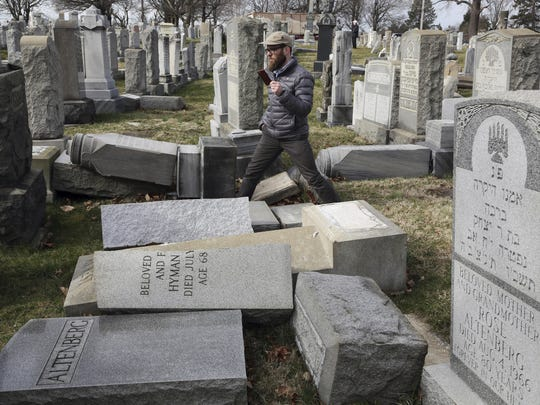 FILE - In this Feb. 27, 2017, file photo, Rabbi Joshua Bolton of the University of Pennsylvania's Hillel center surveys damaged headstones at Mount Carmel Cemetery in Philadelphia. The shooting rampage that killed more than 10 people at Pittsburgh's Tree of Life Synagogue on Saturday, Oct. 27, 2018, is being decried as the deadliest attack on Jews in U.S. history. Yet the carnage, however unprecedented, is not an aberration: Year after year, decade after decade, anti-Semitism proves to be among the most entrenched and pervasive forms of hatred and bigotry in the United States. (AP Photo/Jacqueline Larma, File)