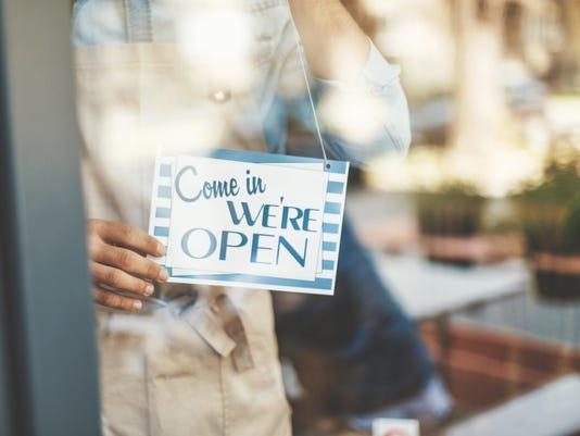 Man placing open sign on cafe door