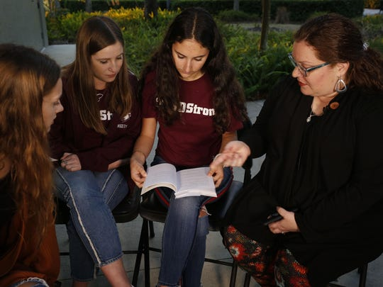 "In this Wednesday, Jan. 16, 2019, photo, Brianna Jesionowski, from far left to right, Brianna Fisher and Leni Steinhardt sit during an interview with The Associated Press as journalism teacher Sarah Lerner, right, makes a point regarding the new book called ""Parkland Speaks: Survivors from Marjory Stoneman Douglas Share Their Stories,"" in Parkland, Fla. Students and teachers from the Florida school where 17 died in February's high school massacre wrote the raw, poignant book about living through the tragedy. (AP Photo/Brynn Anderson)"