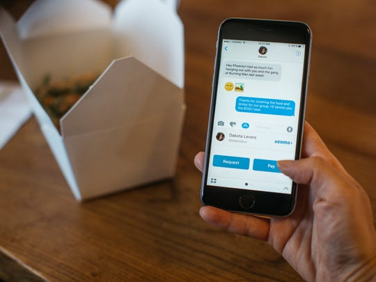 A person holding a smartphone while it displays the Venmo app. Chinese food container on the table in the background.