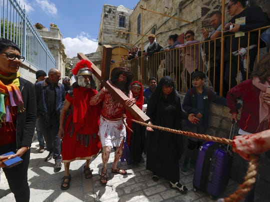 An actor dressed as Jesus Christ carries a cross as