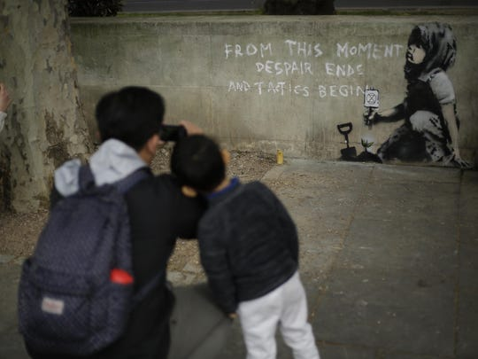 A passing tourist takes picture of a new piece of street art that people noticed for the first time last night and is believed to be by street artist Banksy on a wall where Extinction Rebellion climate protesters had set up a camp in Marble Arch, London, Friday, April 26, 2019.