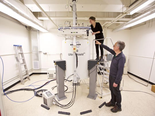Graduate student Anna Duell, top, and Dr. David Peyton collect samples from a nuclear magnetic resonance spectrometer in a lab at Portland State University in Portland, Ore., April 16, 2019.