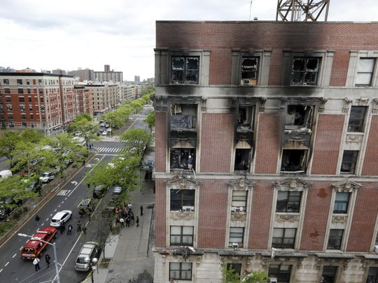 Fire marshals sift through a burned out apartment in New York's Harlem neighborhood, Wednesday, May 8, 2019. Six people, including four children, were killed Wednesday.