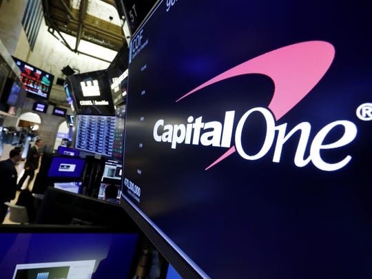 The logo for Capitol One Financial appears above a trading post on the floor of the New York Stock Exchange, Tuesday, July 30, 2019. A security breach at Capital One Financial, one of the nation's largest issuers of credit cards, compromised the personal information of about 106 million people, and in some cases the hacker obtained Social Security and bank account numbers. (AP Photo/Richard Drew)