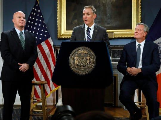 New York City Police Commissioner James O'Neill, left, listens as his successor, Chief of Detectives Dermot Shea, center, speaks at New York City Hall on Monday, alongside Mayor Bill de Blasio.