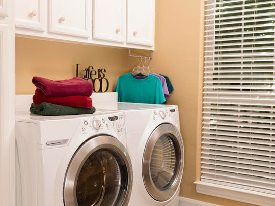 Laundry room with towels folded and clothes hung to dry. Modern, energy-efficient washer and dryer appliances.