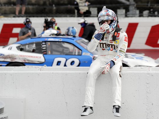 Kyle Busch sits on the wall as Chase Briscoe celebrates behind him after Briscoe edged out Busch to win the NASCAR Xfinity series auto race Thursday in Darlington, S.C. (AP Photo/Brynn Anderson)