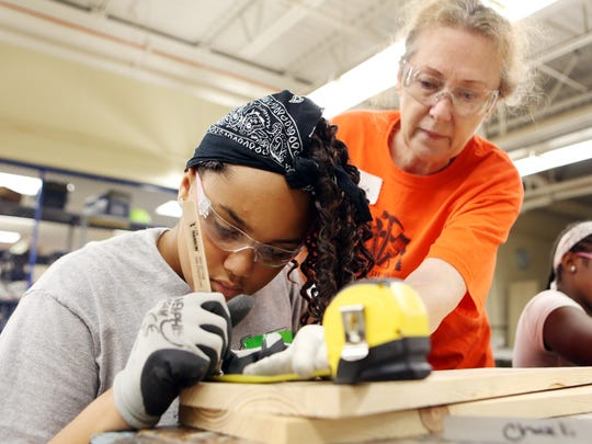 Charli Singleton, 13, of Springdale gets help from Rebecca Thompson during Rosie's Girls summer boot camp. The program is designed to give girls 11-13 an introduction to STEM-related careers and build self-esteem.