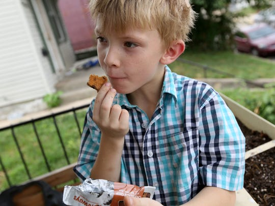 Timmy Dyas, 6, Newport, eats an oatmeal bar he got at school. It was funded by Freestore Foodbank.  The Enquirer/Cara Owsley
