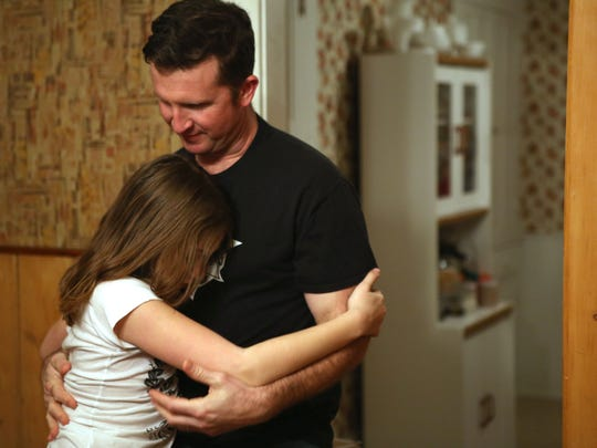 """Jason embraces his daughter after they made dinner together in their home in Yellow Springs. He said, """"I am really happy that Zay is with us because we are going to try and protect her. There is hurt in everybody's life. There's hurt in the world...but that hurt of not being accepted by your family is not going to be something she has to deal with."""""""
