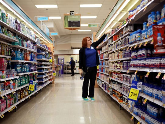 Britney McGannon, a Kroger general-merchandise manager, organizes products on a shelf. She transitioned on the job and now proudly wears the female uniform and a new name tag.