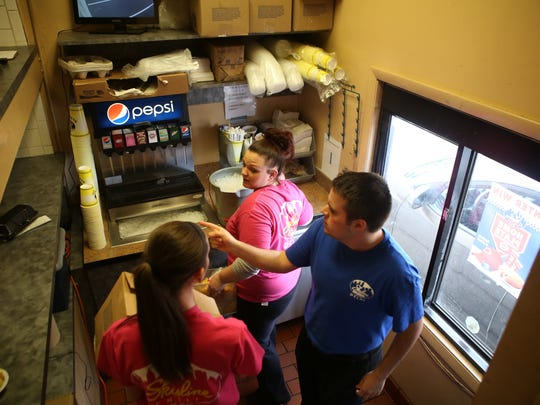 Ashton Dotson works the drive-thru window at Skyline in Delhi on Sunday, March 15, 2015 with help from his co-workers Tori Anderson and Kristen Dunn. During Ashton's shift from 5-11 PM, there was a constant line of cars ordering food.