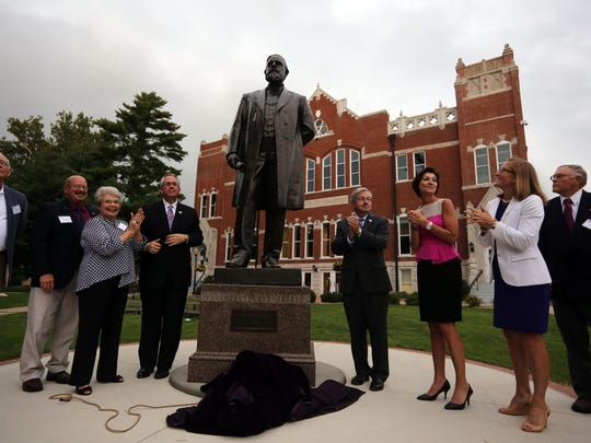 Iowa Wesleyan College President Steven Titus, center left; Gov. Terry Branstad, center right; Lt. Gov. Kim Reynolds, third from right; and other officials and family members of former U.S. Sen. James Harlan, applaud during an unveiling ceremony for the 19th century senator's statue on the Iowa Wesleyan College campus in Mount Pleasant in 2014. The Harlan statue had previously stood at the U.S. Capitol for more than a century.