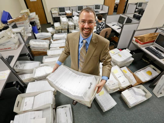 Polk County Auditor Jamie Fitzgerald is surrounding by some of the 26,000 absentee ballots that his office is handling as part of early voting in 2012. Early voting for the 2014 begins Thursday.
